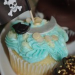 vanilla cupcake, blue and white butter icing, sugar paste, fondant cutlass, gold coins, pirate theme