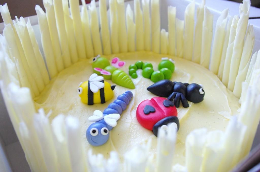 purple velvet cake, cream cheese icing, handmade sugarpaste bugs, white chocolate scrolls, insects