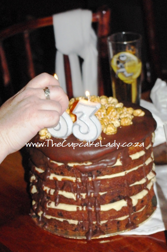 peanut butter chocolate cake with caramel popcorn and chocolate toffee ganache