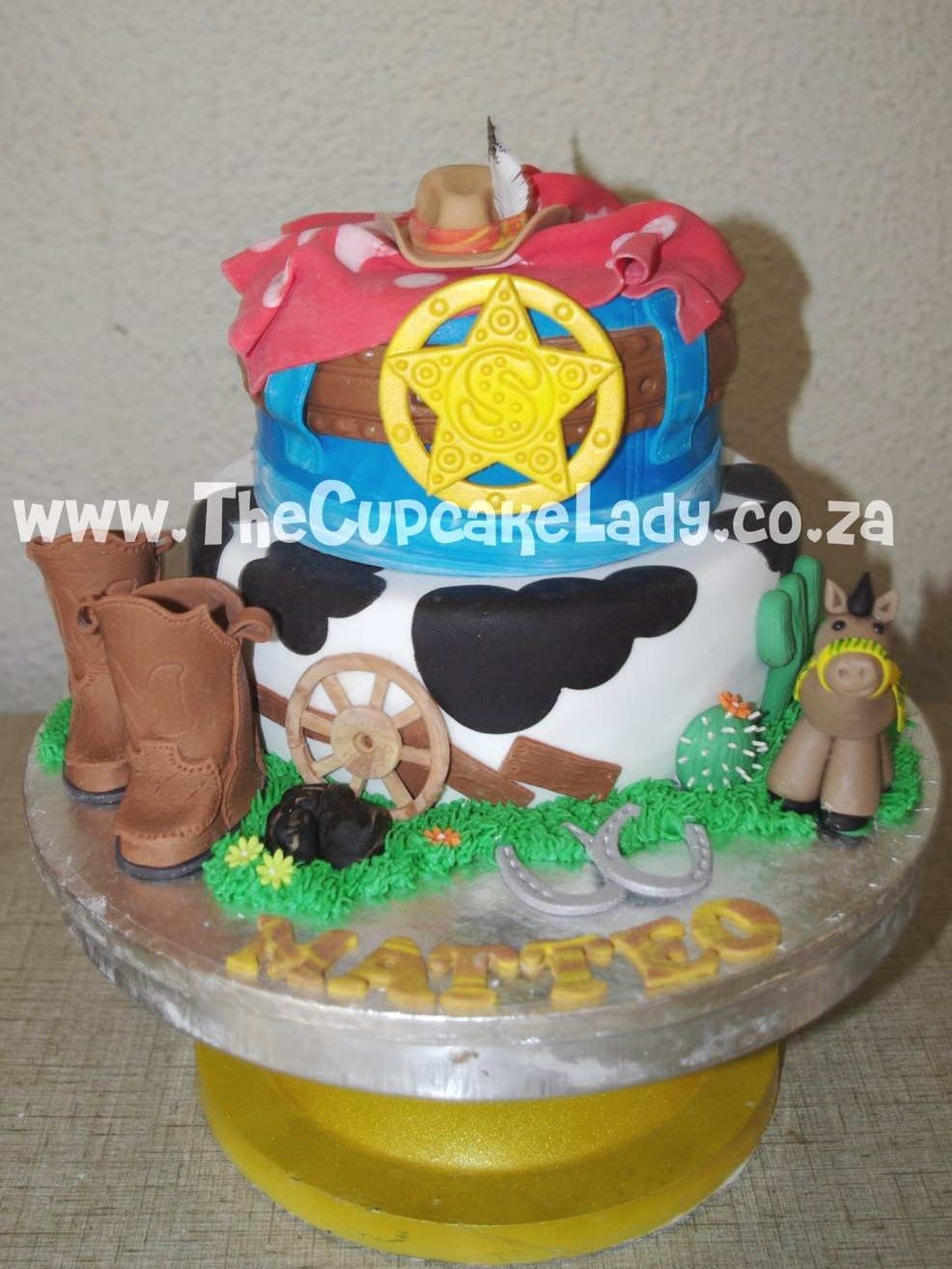 cowboy theme, western theme, two tier cake, birthday cake, custom made sugar paste fondant decorations - bandana, stetson, pony, boots, wagon wheel, sheriff badge buckle, horseshoes, cactii
