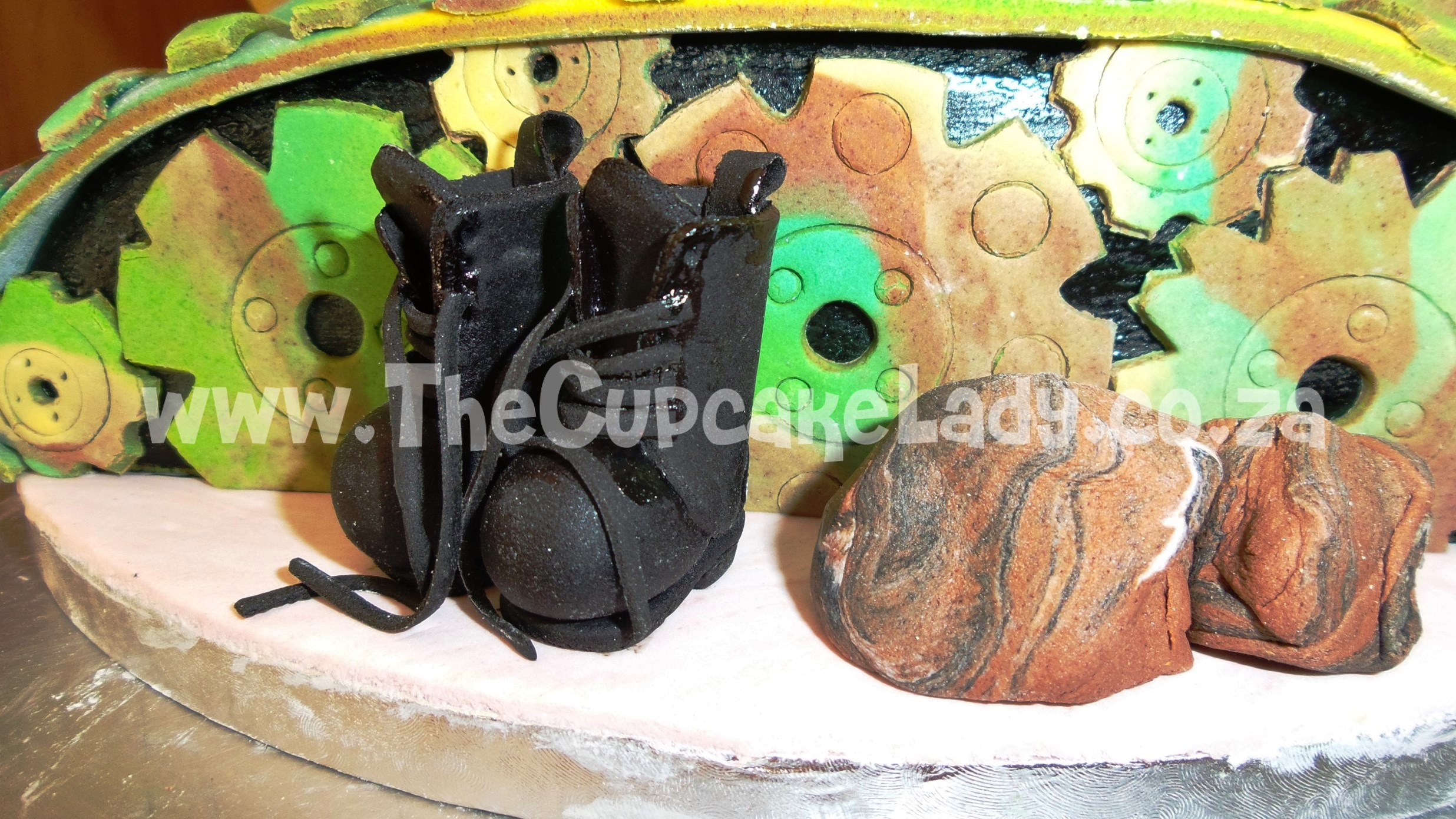 Custom made, sugar paste boots and rocks, sugar paste soldier tank driver wearing a beret, tank cake, army cake, novelty cake, sculpted cake, green yellow brown colour scheme, camouflage