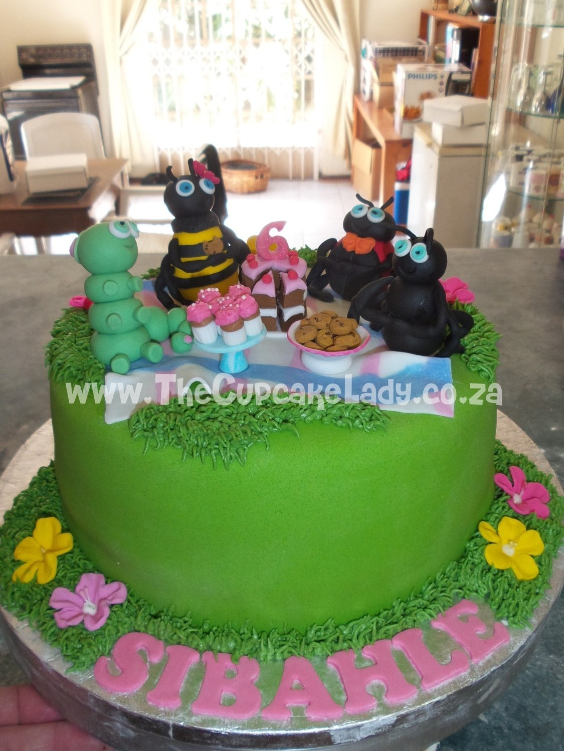 layers of vanilla cake & pink velvet cake, cream cheese icing, caramel icing, handmade sugar paste bugs picnic. Sugar paste cake, cupcakes, cookies and the plates