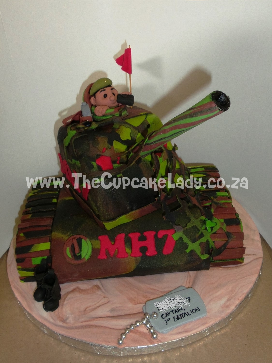 birthday tank-shaped cake, the driver of the tank is wearing a beret and holding a pair of binoculars, custom sugar art