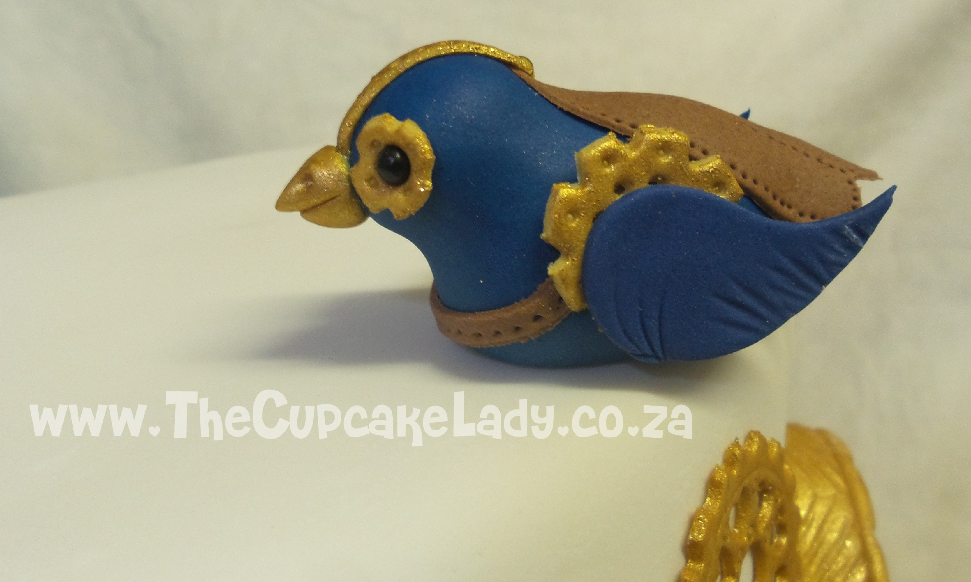 This birthday cake is two-tiers of vanilla cake with vanilla butter icing, decorated with custom made Steampunk themed accents in blue and gold - cogs and wheels, a pocket watch, lady bug, butterfly, bird, key, feathers and roses.