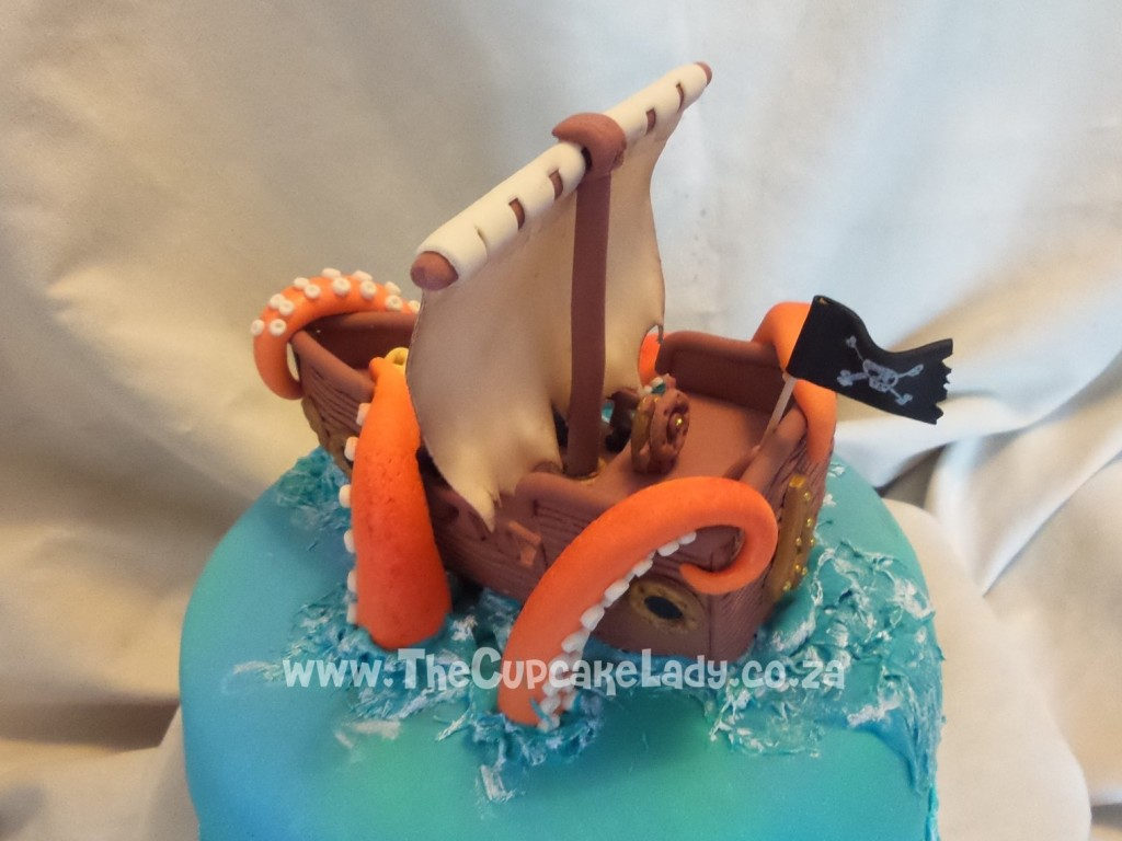 This is a handmade sugar paste pirate ship and giant squid tentacles for a birthday cake
