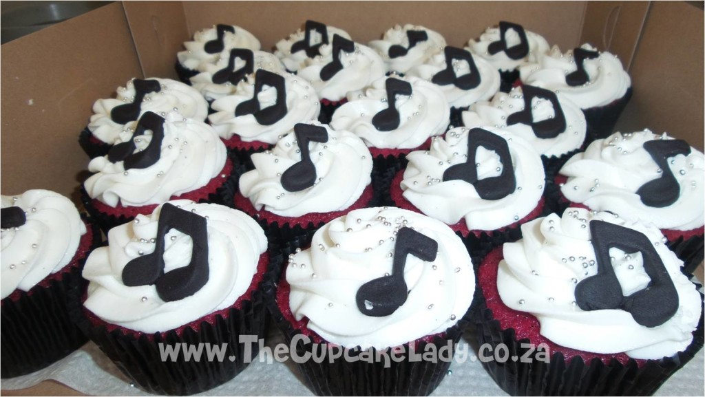 red velvet cupcakes in black paper cups were topped with white vanilla butter icing and decorated with black, sugar paste music notes
