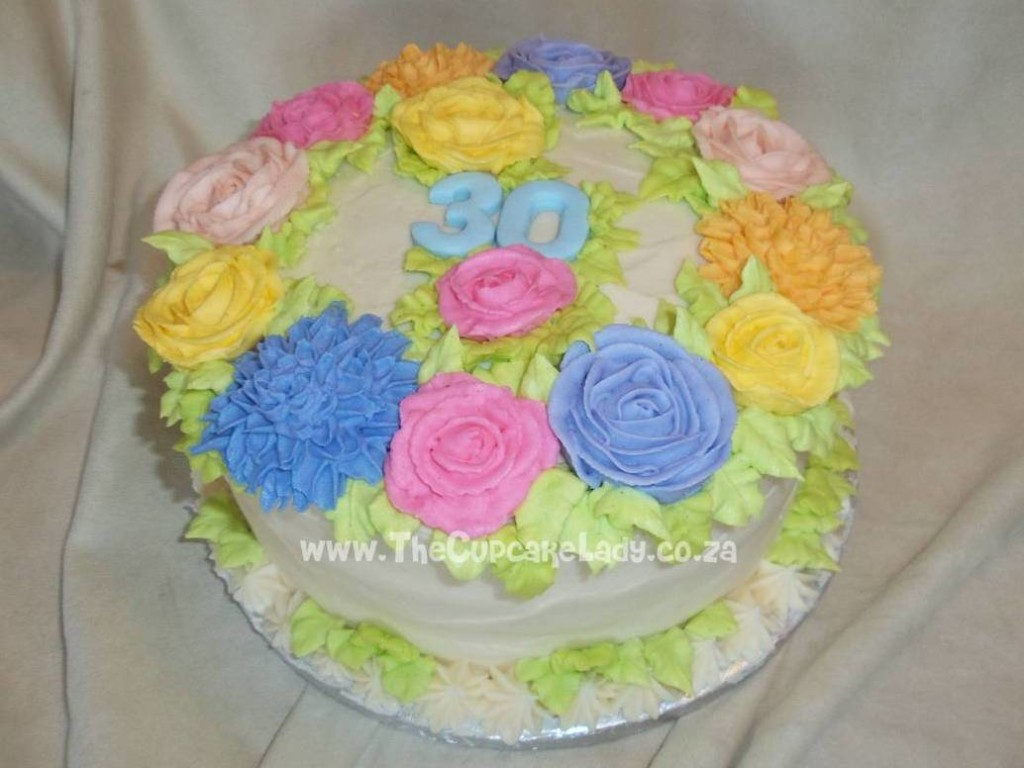 carrot cake with cream cheese icing, decorated with butter icing flowers
