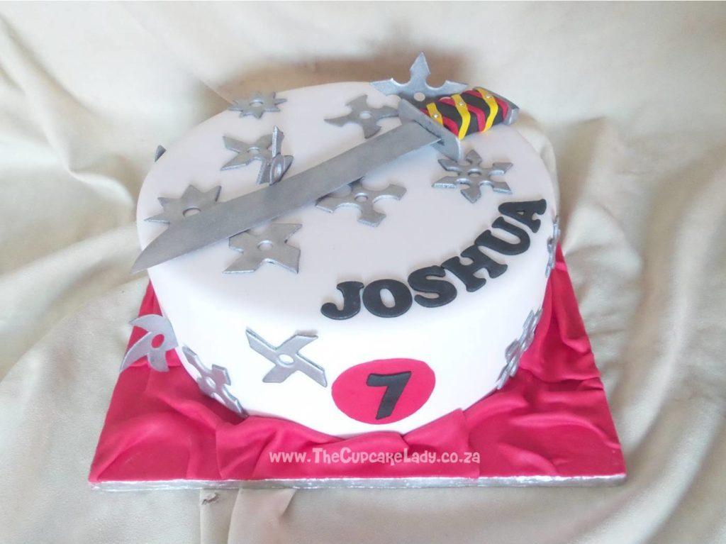 ninja themed birthday cake decorated with sugar paste throwing stars and katana