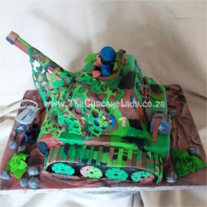 Tank-shaped novelty cake, complete with binocular wielding occupant, camo-nets, water tanks and a shovel on the back