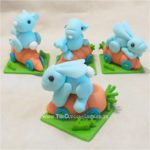 """My customer fell in love with the skating bunny cake topper made by Sugar High, Inc., so I put my own """"spin"""" on it and made these little fondant bunnies for her! :D The green squares are 6x6cm and I was terrified to touch their ears after they were assembled!! :P"""