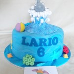 single tier vanilla cake, with a hand made sugar paste dolphin, beach ball, coral and seashells as removable cake topper